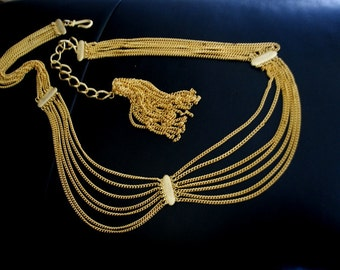 Flapper style vintage 80s gold tone metal , drapery , cascade  multichain belt- necklace with a large tassel.