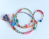 Bright and colourful single strand double wrap bracelet or choker lariat necklace with tassel and evil eye protection bead