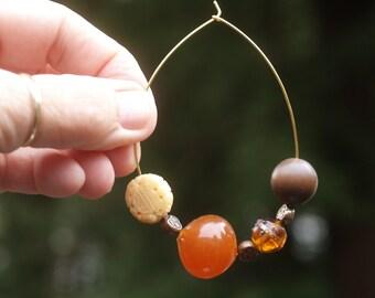 Huge gold-tone hoop earrings w/ metal findings, glass, lampwork, and carved ivory beads.