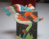 Colorful art deco die cut 1931 Buzza christmas bridge tally card deco lady downhill skiing in elaborate  and matching big scarf