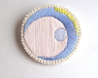 Hand embroidered brooch round asymmetrical geometric with pastel colors of pink, lavender, and yellow Pantone color of the year