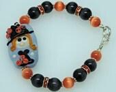 MISS WITCH on BLUE:  Artist Lampwork Glass Black and Orange Bracelet Halloween