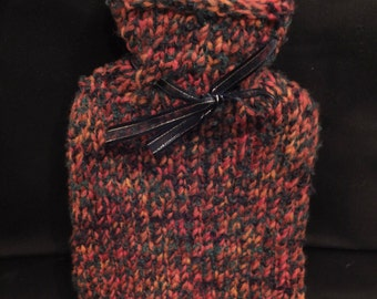 Hot water bottle with hand knitted cover