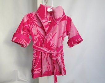 A terry cloth baby robe suitable for the bath or beach.  0-9 month size in vibrant pink.