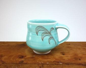 Aquamarine glazed porcelain mug with flourish