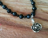 Silver tone rose pendant on black bead necklace