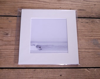 Black and white photographic image of surfer in a mount