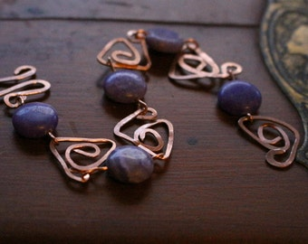 purple glass bead bracelet with hammered copper geometric links