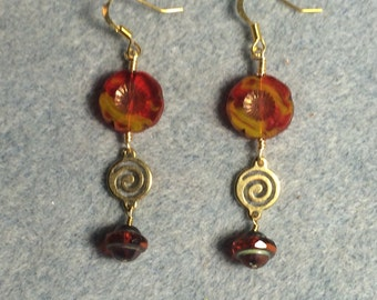 Red and yellow Czech glass pansy bead dangle earrings adorned with gold swirly connectors and reddish Czech glass Saturn beads.