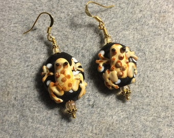 Black and tan lampwork frog bead earrings adorned with tan Czech glass beads.