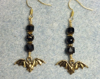 Gold bat charm earrings adorned with black Czech glass beads.
