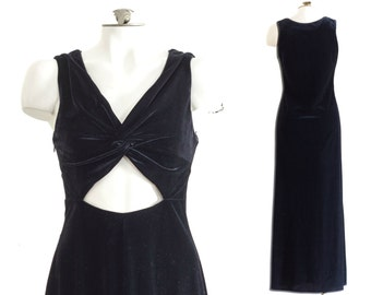 Sleeveless black velvet gown with triangle cut out at abdomen