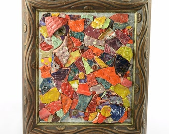 Ceramic mosaic abstract multicolor shades of red orange yellow on coated medium of dictionary with rustic vintage page