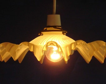 Cream colored glass shade for pendant light with fluted swirls