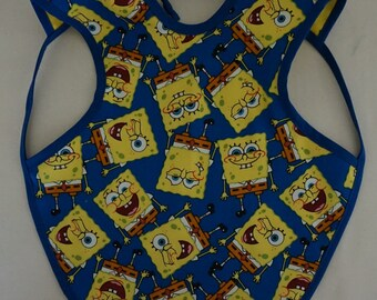 Sponge Bob child's bib that covers a large part of their body.  Reversible with cotton on one side and flannel on the other.