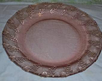 A Vintage Pink Glass Dinner Plate with grape designs.