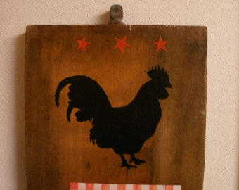 Black rooster on barn wood