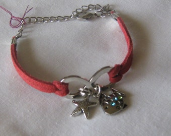 Red suede bracelet with star fish and jeweled fish.