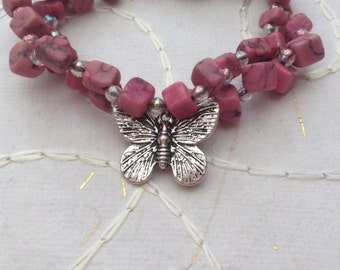 Pink stone beaded and clear glass beaded handmade elasticated double bracelet with a silver metal butterfly charm