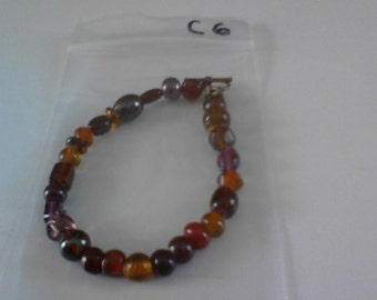 Bracelet with various shades of dark amber beads c6