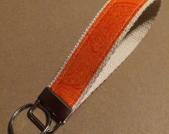 Orange paisley key fob or zipper pull on natural cotton webbing