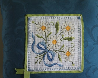 Blue throw pillow with cross_stiched daisies