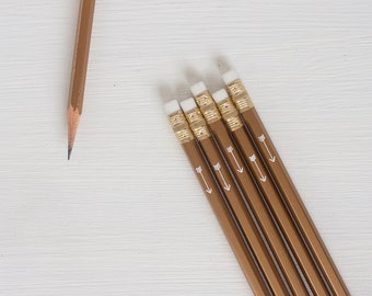 8 gold pencils with white arrow