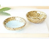 Pair of two small resin salt and pepper spice pinch trinket dish bowls in pale pastel blue and gold glitter sparkle.