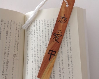 To be in love in Japanese calligraphy on a wooden bookmark with a white tassel