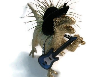 Singing cowboy dinosaur planter with air plant, guitar and hat.