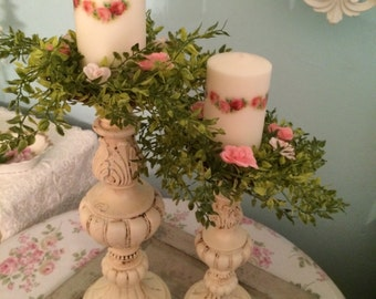 A pair of tall Pillar ornate satin ivory candle holders can be distressed