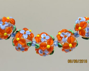Set of 5 Handmade Lampwork Orange Flower beads with Blue Floral Blooms.