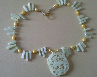 REBIRTH : pale green jade Phoenix pendent on matching necklace.