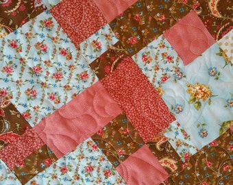 Crazy Eights is this beautiful brown, aqua and mauve quilt with roses