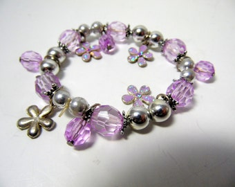 Ladies' charm bracelet with round silver beads, large lavender faceted beads, and glittery flower charms