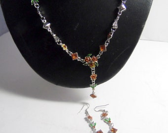 Silvery chain link necklace with brown glass beads, flower beads, and tiny enameled leaves. Comes with matching earrings