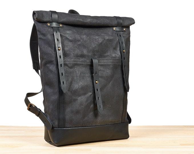 Slim waxed canvas backpack. Dark grey canvas, black leather rucksack.