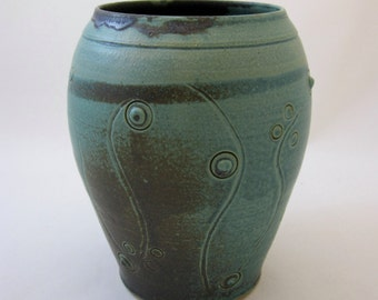 Wheel-thrown, hand carved with slip-trail decoration antique green/black glaze.