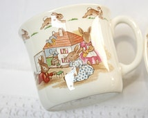 TWO sweet  pieces of Royal Doulton Bunnykins china: bowl and mug, the Bunny family watching TV together and playing with their doll's house