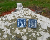 Vintage pair of cuff links blue and white Egyptian hieroglyphic art surreal design inset in brass metal mythology music rocker fashion