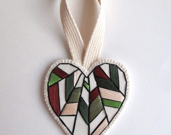Valentine's Day heart ornament hand embroidered in earthy colors of greens, brown, eggshell white and burgundy on bright cream muslin