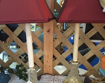 A pair of Tall glass bottom candle stick lamp with dark red shades