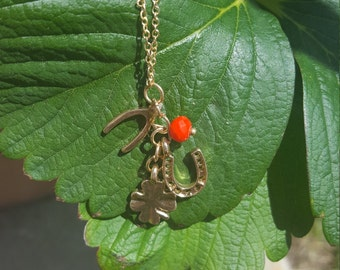 Lucky Charm Necklace with Gold Four Leaf Clover, Horseshoe, and Wishbone Charms and a Small Red Orange Bead on Gold Thin Chain