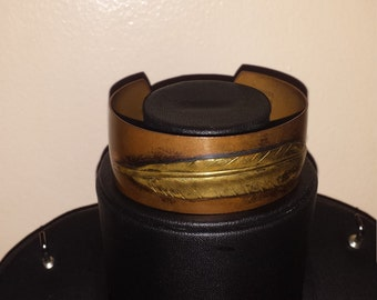 A boho chic copper cuff bracelet with feather design