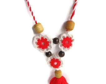 Suspension on the neck of red and white thread and wooden beads.