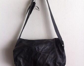 Black large shoulder bag on a long strap, a bag made of genuine leather.