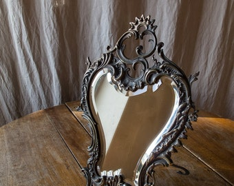 Old antique bronze mirror with beveled glass