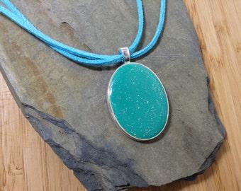 A turquoise blue enamel pendant.