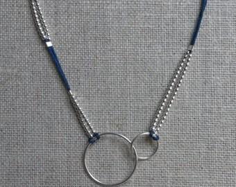 Asymmetrical collar, double silver circle on dark blue silk-polyester cord