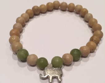 Wood beaded bracelet with for green beads and one silver elephant
